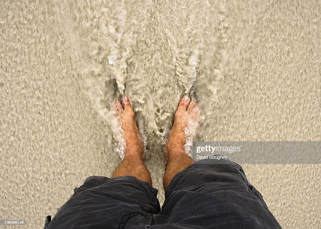 Male legs in surf on beach : Stock Photo