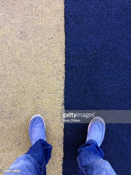 male legs on yellow and blue surface. - gummihose stock-fotos und bilder