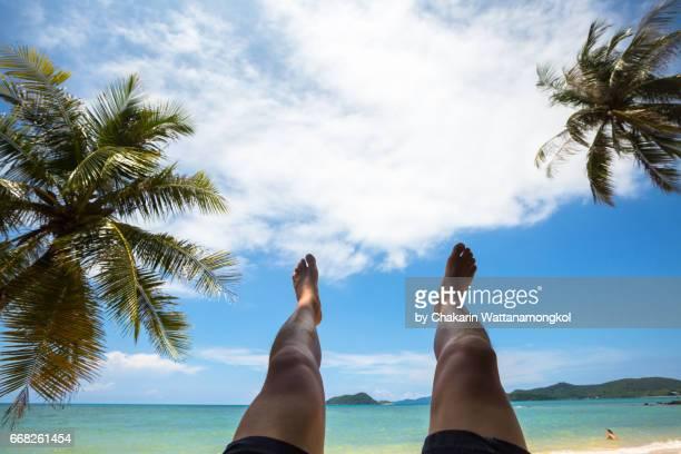 Male legs raising into blue sky - White Sand Beach.