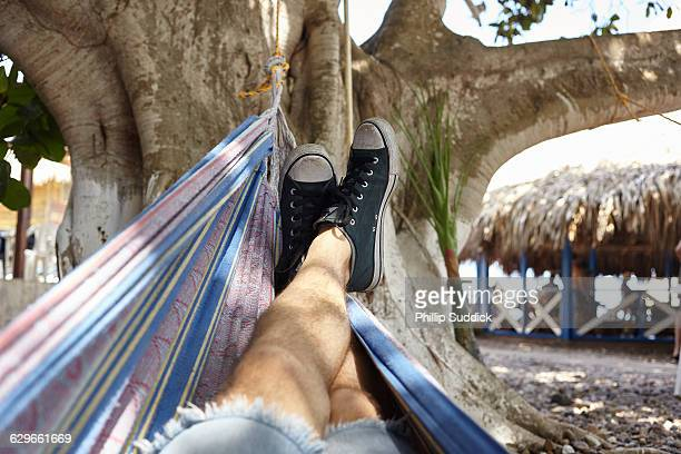 male legs relaxing on the beach POV