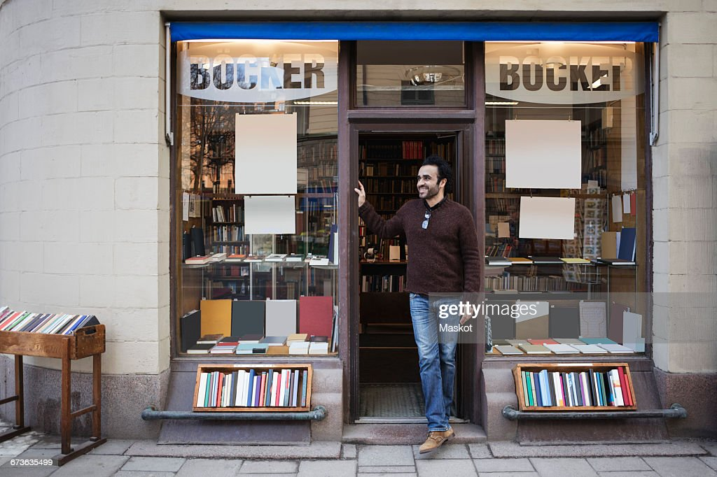 Male librarian looking away while standing at doorway : Stock Photo