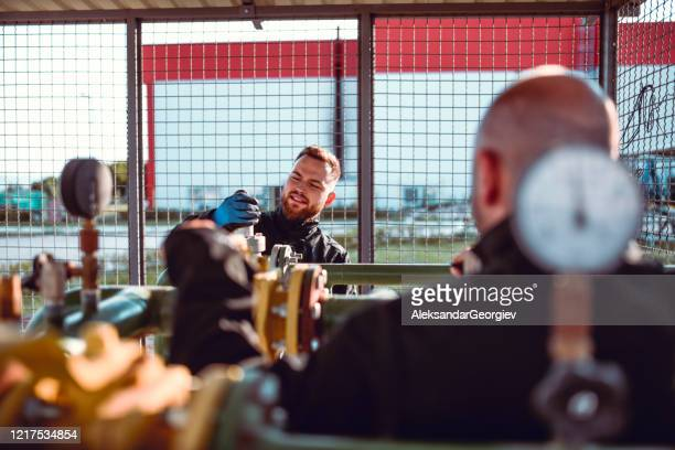 male liquified gas store workers checking valve pressure - butane stock pictures, royalty-free photos & images