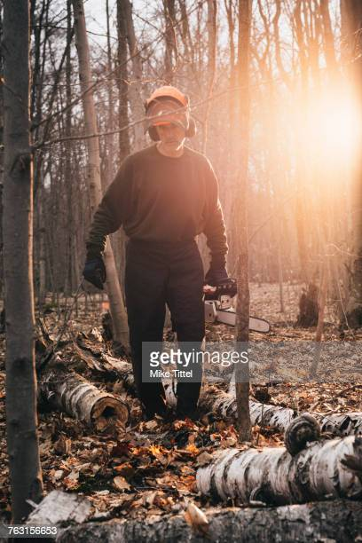 Male logger carrying chainsaw in sunlit autumn forest