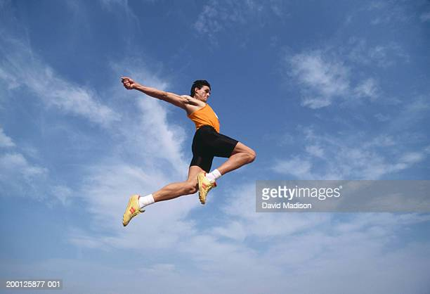 Male long jumper in mid-air, low angle view