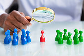 Male Looking At Colorful Pawns With Magnifying Glass