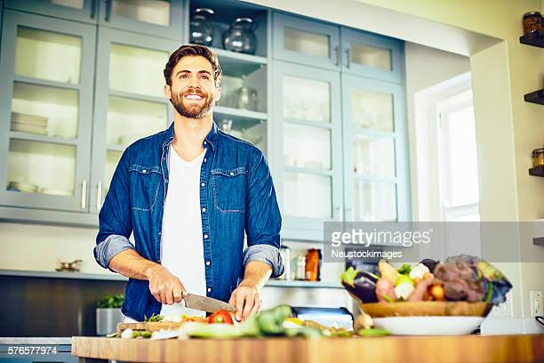 Male looking away while cutting vegetables at kitchen island