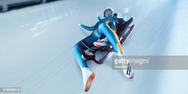 couple de lugeurs mâle tomber du traîneau sur la piste de luge - événement sportif d'hiver photos et images de collection