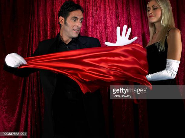 Male magician performing on stage, aided by young female assistant