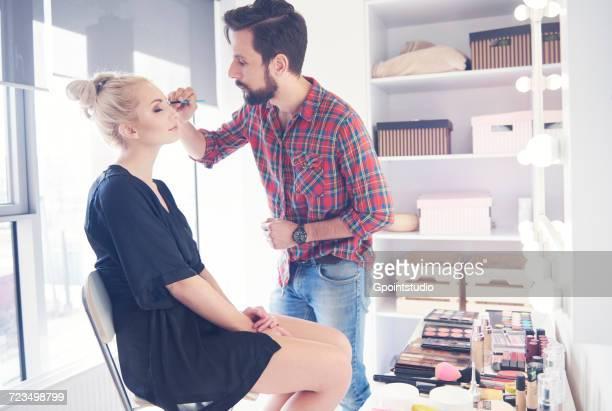 male make up artist applying eyeliner to model for photo shoot - アイメイク ストックフォトと画像