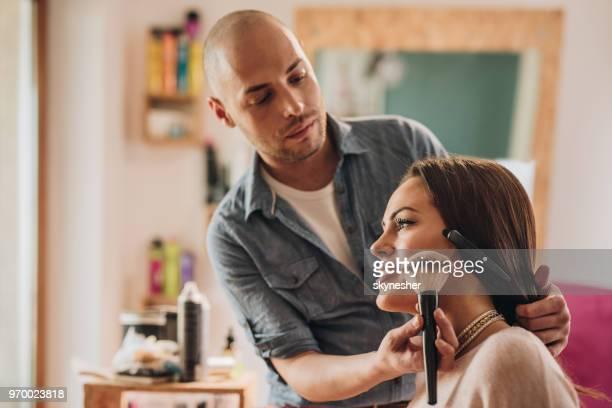Male make-up artist applying blush on young woman's cheek.