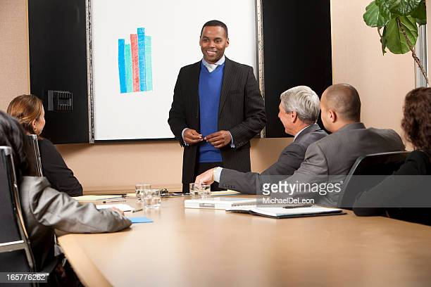 Male making business presentation with bar graph behind him