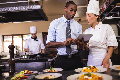 Male manager and female chef using digital tablet in kitchen 1094919124