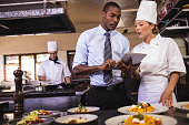 Male manager and female chef using digital tablet in kitchen