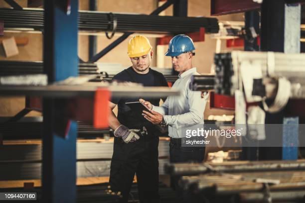 macho manager e serrurier cooperando enquanto estiver usando o touchpad em um armazém. - metalúrgico - fotografias e filmes do acervo