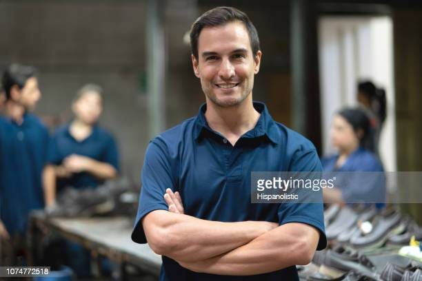 Male manager at a shoe factory smiling at camera with arms crossed and people working at background