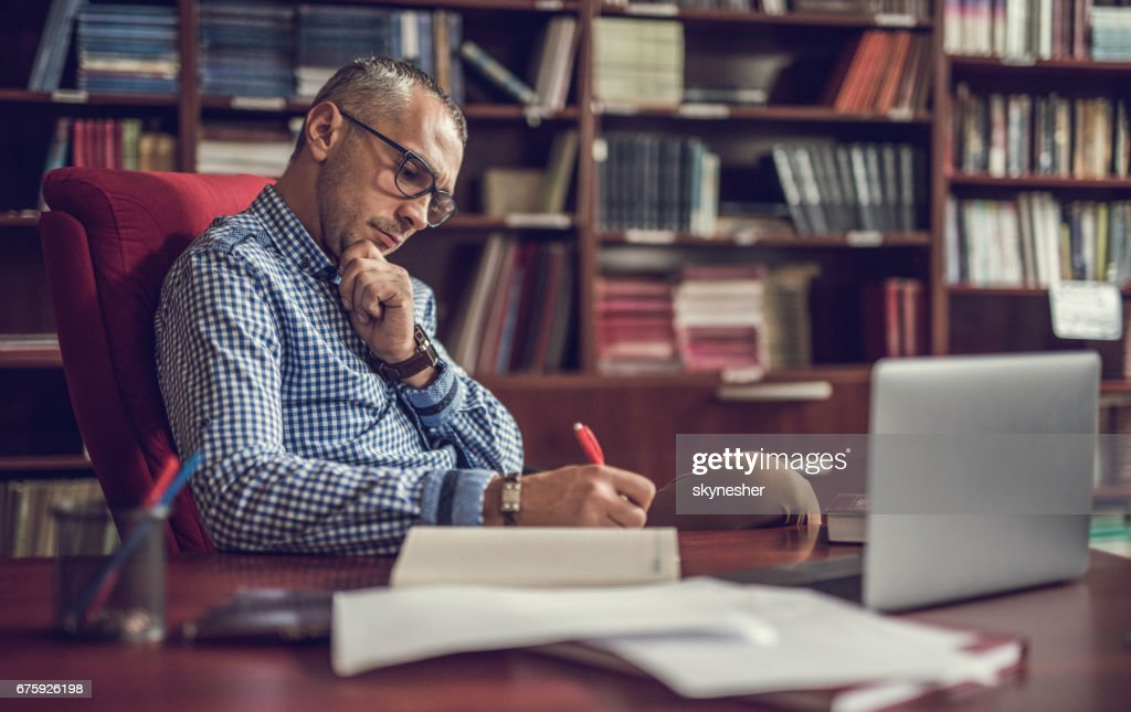 Male manager taking notes in home office. : Stock Photo