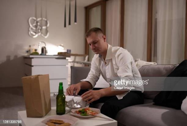 male manager unwrapping takeaway food - alcohol stock pictures, royalty-free photos & images