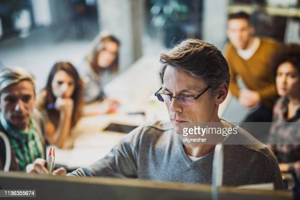 male manager writing plans to his team during presentation in the office. - incidental people stock pictures, royalty-free photos & images