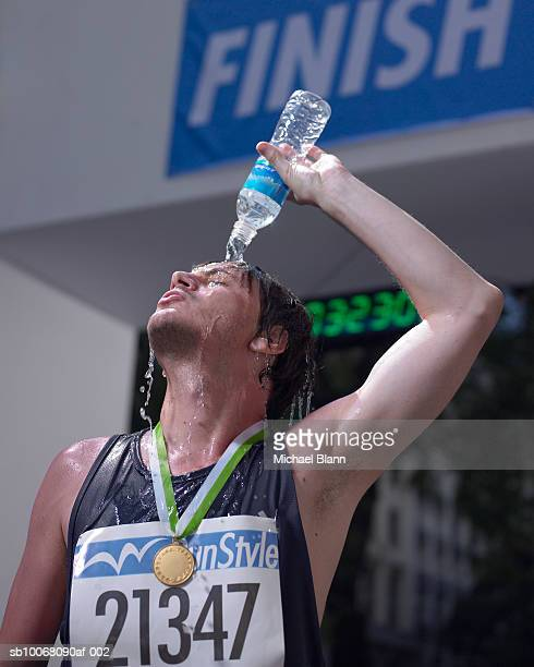 Male marathon runner pouring water from bottle over body