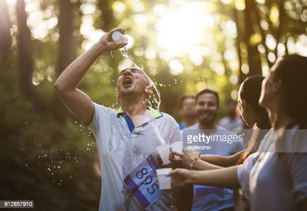 male marathon runner refreshing himself while pouring water on his face. - thirsty stock pictures, royalty-free photos & images