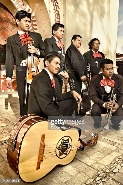 banda mariachi macho posando en cobble calles al aire libre - mariachi fotografías e imágenes de stock