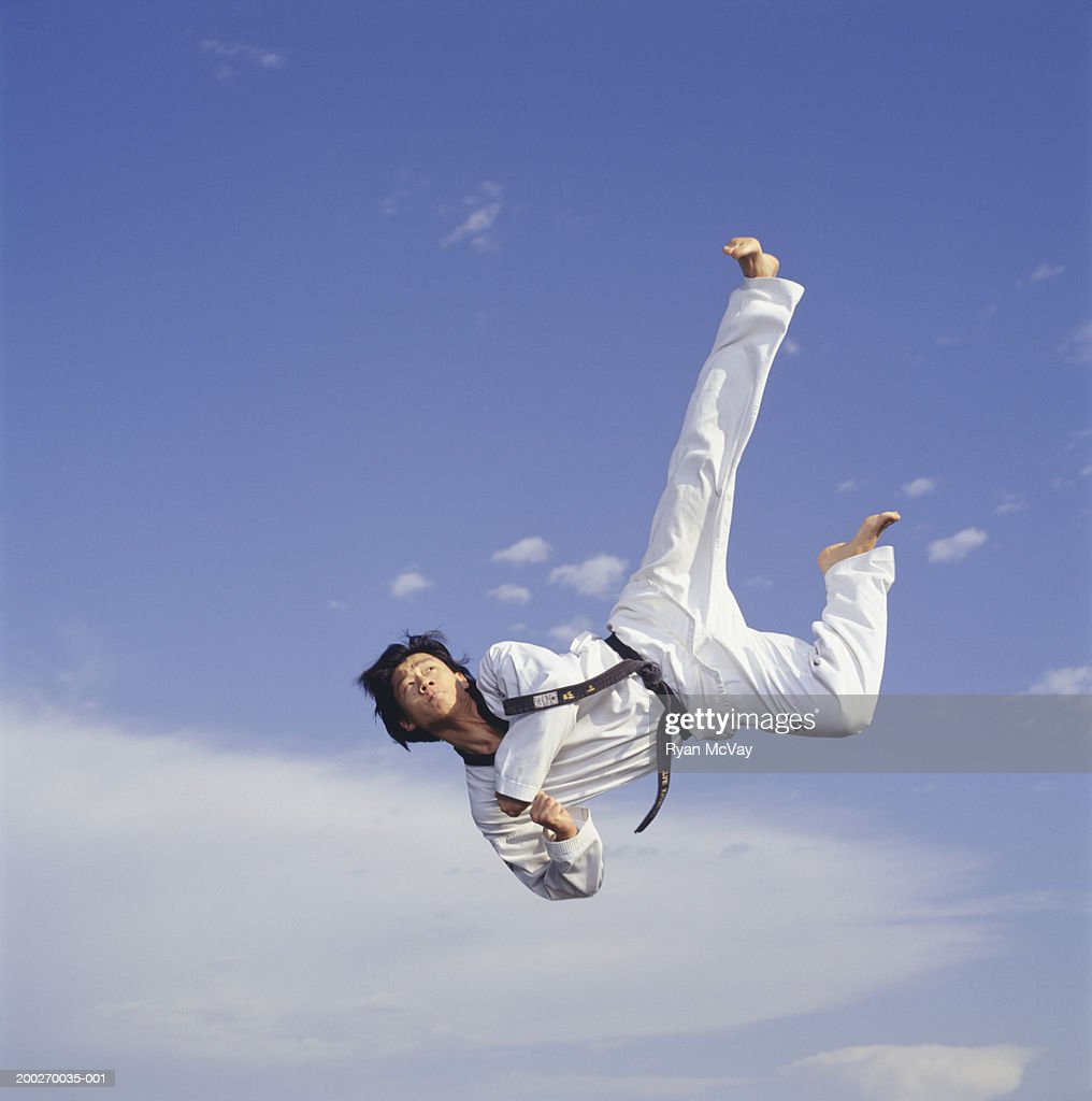 Male martial artist, mid-air, low angle view : Stock-Foto