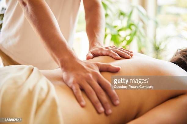 male massage therapist work on a woman's back - pressure point stock photos and pictures
