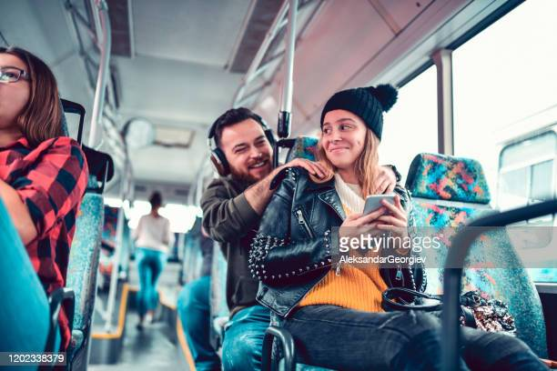 male massaging his female friend while listening to music on a bus trip - massage funny stock pictures, royalty-free photos & images