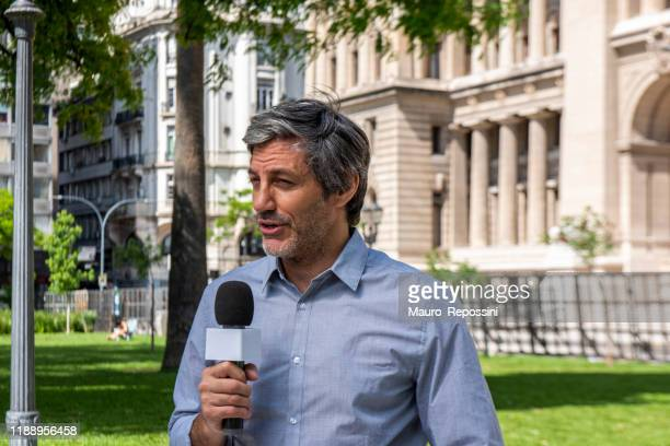 male mature reporter talking and holding a microphone in a public park during a sunny day at buenos aires, argentina. - live event stock pictures, royalty-free photos & images