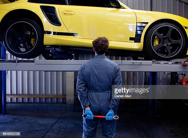 male mechanic checking yellow sports car, holding socket wrench behind his back, rear view - combinaison de protection photos et images de collection