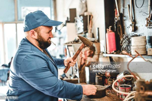 male mechanic smoking cigarette and fixing part with hammer - strike industrial action stock pictures, royalty-free photos & images