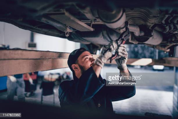 male mechanic tightening screw on car exhaust - chassis stock pictures, royalty-free photos & images