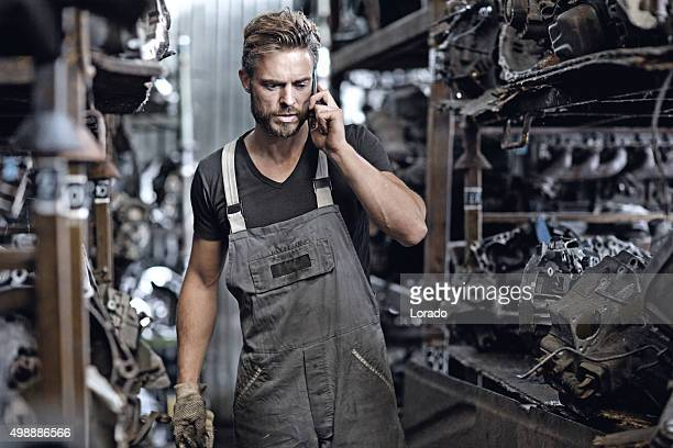 male mechanic working at junkyard storage