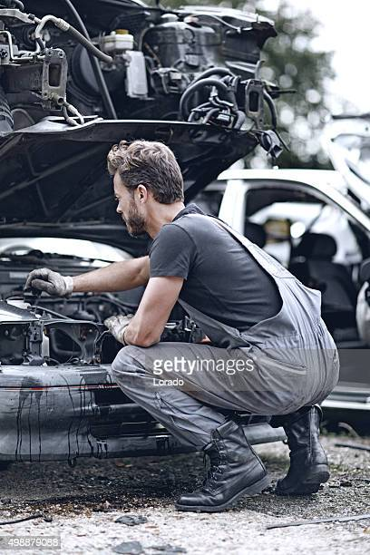 male mechanic working on destroyed car - junkyard stock photos and pictures