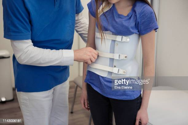 male medical healthcare worker helping a teenager to position a back brace worn for scoliosis correction - scoliosis stock photos and pictures