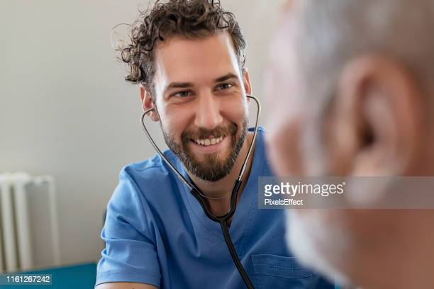 male medical using stethoscope - male nurse stock pictures, royalty-free photos & images