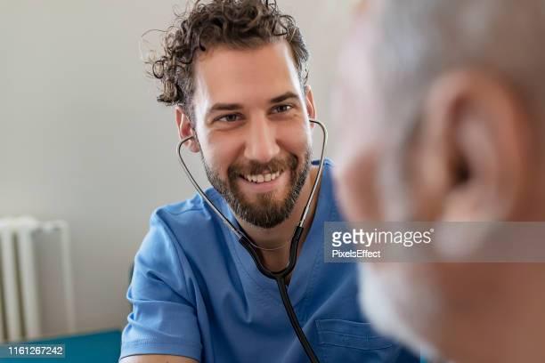 médecin mâle utilisant le stéthoscope - infirmier photos et images de collection