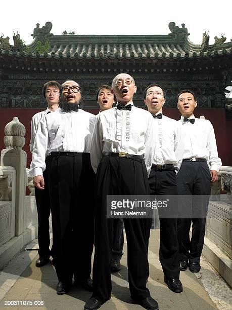Male members of choral group practicing on bridge