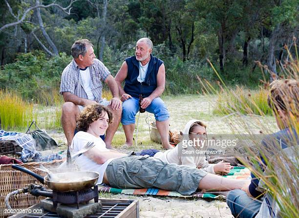 Male members of family relaxing outdoors, fish cooking in pan