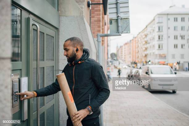 male messenger holding package while ringing intercom of building - ringing doorbell stock pictures, royalty-free photos & images