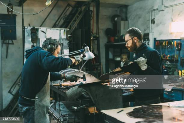Male metalworkers hammering copper at forge workbench