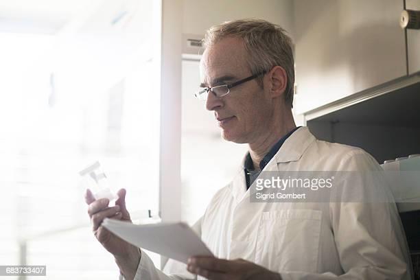 male meteorologist examining sample bottle in weather station laboratory - sigrid gombert fotografías e imágenes de stock