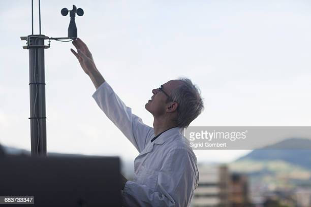 male meteorologist measuring wind using anemometer at weather station - meteorology stock pictures, royalty-free photos & images