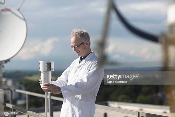 male meteorologist monitoring meteorological equipment at rooftop weather station - sensor stock pictures, royalty-free photos & images