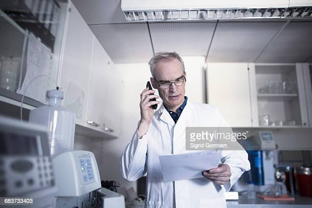male meteorologist reporting data on smartphone at weather station laboratory - sigrid gombert stock pictures, royalty-free photos & images