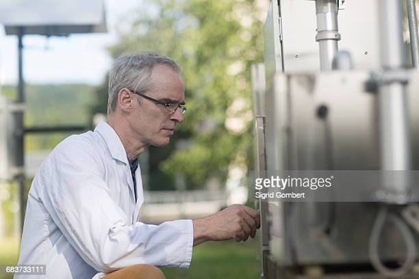 male meteorologist unlocking outdoor weather station equipment - sigrid gombert stock pictures, royalty-free photos & images