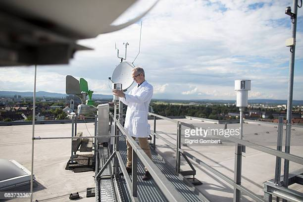 male meteorologist updating meteorological equipment measurements at rooftop weather station - sigrid gombert stock pictures, royalty-free photos & images