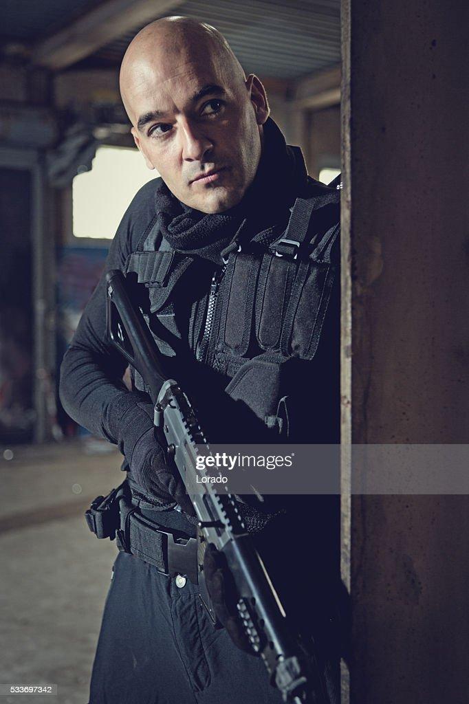Uomo militare si consideri parte di un membro del team che tiene in magazzino abbandonato di fucile : Foto stock