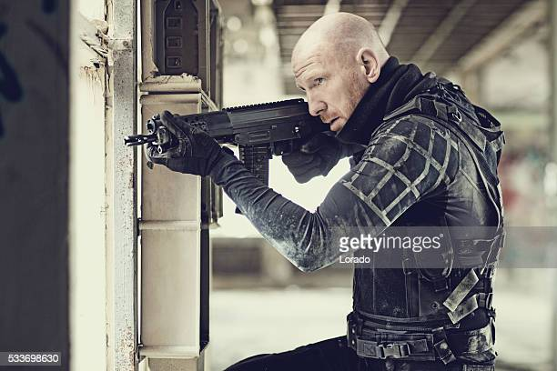 Male military swat team member holding rifle in abandoned warehouse