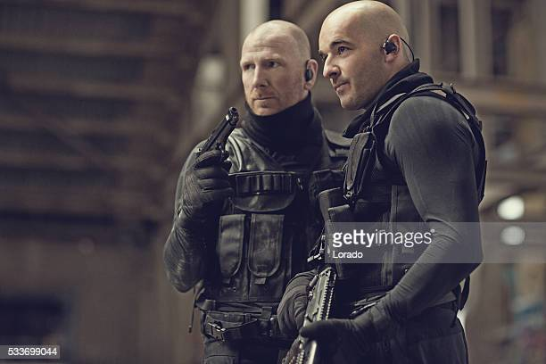 Male military swat team members holding weapons in abandoned warehouse
